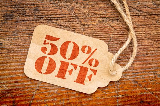 fifty percent off - a paper price tag against rustic wood - sale concept