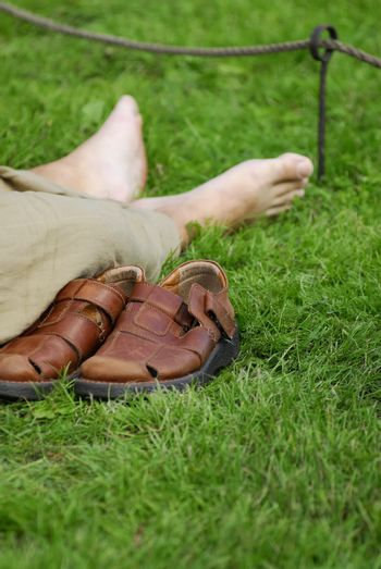 Hiker resting on grass. Shoes off, bare feet.