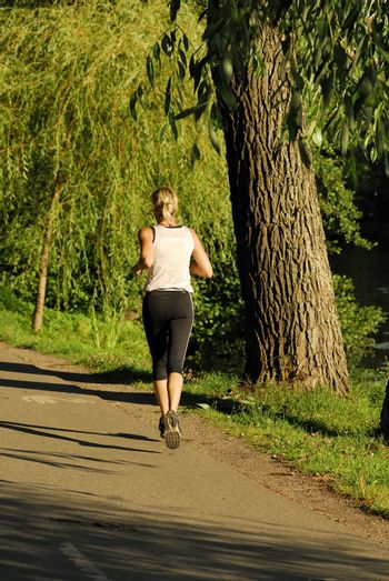 Shot of a female athlete running along a road