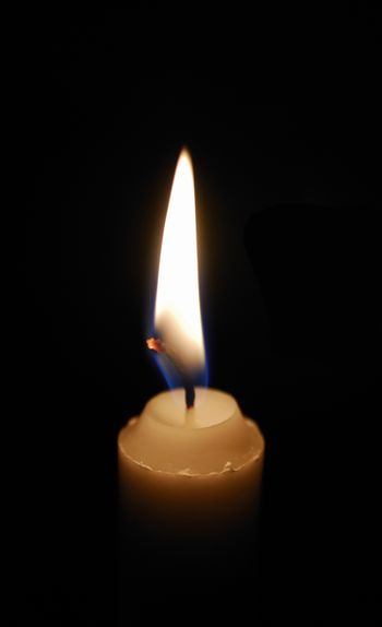 Single lit candle with quite flame on black background.