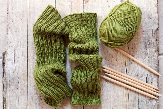 wool green legwarmers, knitting needles and yarn