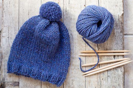 wool blue hat, knitting needles and yarn