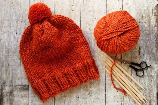 wool orange hat, knitting needles and yarn