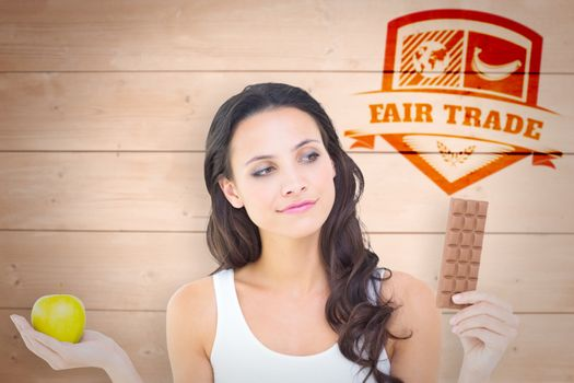 Composite image of pretty brunette deciding between apple and chocolate