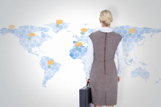 Composite image of back turned businesswoman holding a briefcase