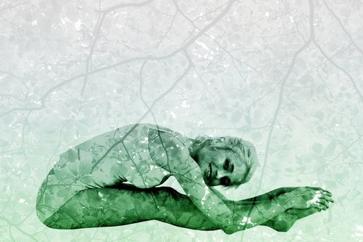 Toned woman doing the paschimottanasana pose against branches and leaves