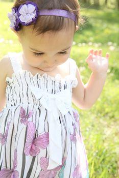 Beautiful brunette toddler outside in the field