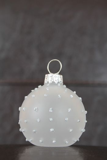 Glass christmas ball against leather and dark wood background