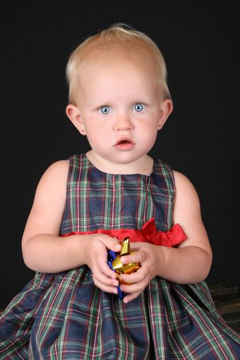 Blonde toddler girl wearing a christmas dress against black