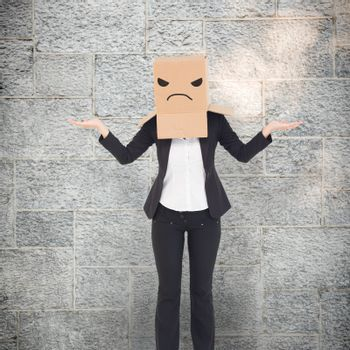 Businesswoman with box over head against grey
