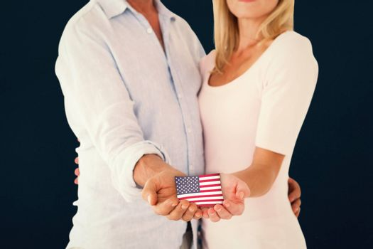 Happy couple holding their hands out against blue background