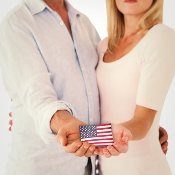 Happy couple holding their hands out against usa national flag