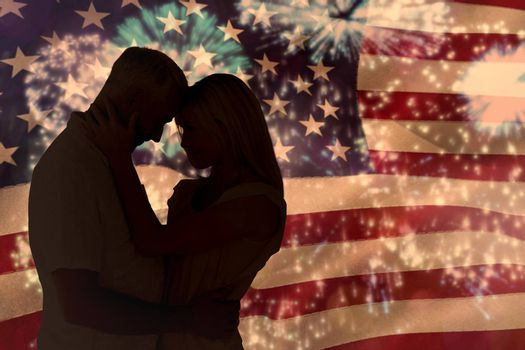 Affectionate couple standing and hugging against colourful fireworks exploding on black background