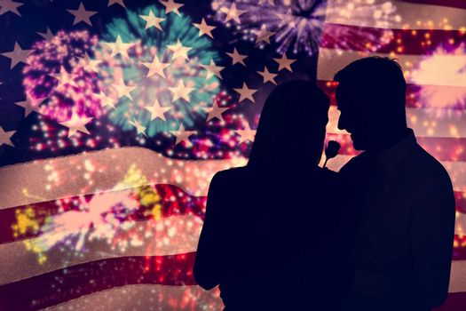 Handsome man giving his wife a pink rose against colourful fireworks exploding on black background