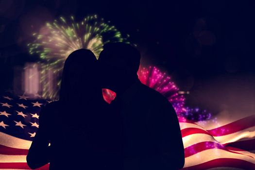 Handsome man giving his wife a kiss on cheek against colourful fireworks exploding on black background