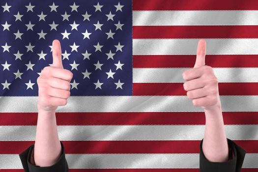 Businesswomans hands showing thumbs up against digitally generated american national flag