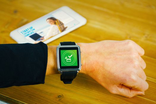 Composite image of businesswoman with smart watch on wrist