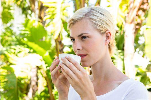 Attractive blonde woman drinking hot beverage