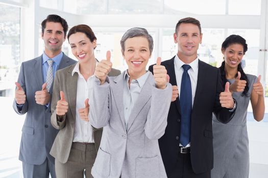 Business people looking at camera thumbs up