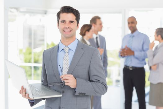 Businessman with his laptop and his colleagues behind