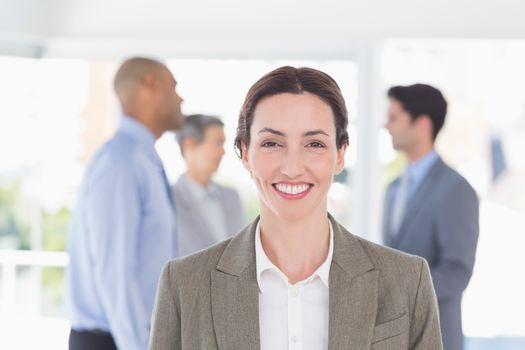 Businesswoman smiling at camera while her colleagues discussing