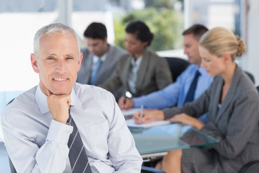Businessman smiling at camera with colleagues behind