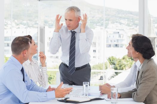 Irritated businessman talking to his team