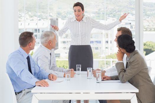 Irritated businesswoman talking to her colleagues