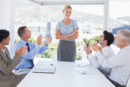 Business team applauding their colleague