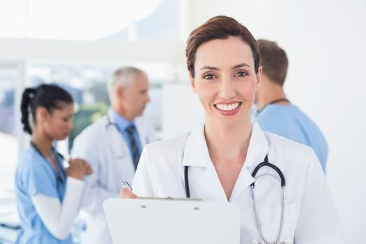 Confident female doctor holding clipboard