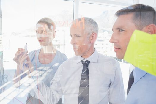 Businessman drawing graph on the glass