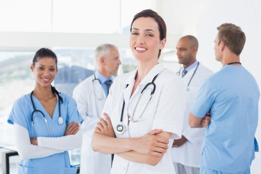 Confident female doctor smiling at camera with her team behind