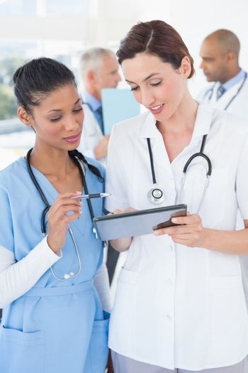 Beautiful female doctors working together with tablet