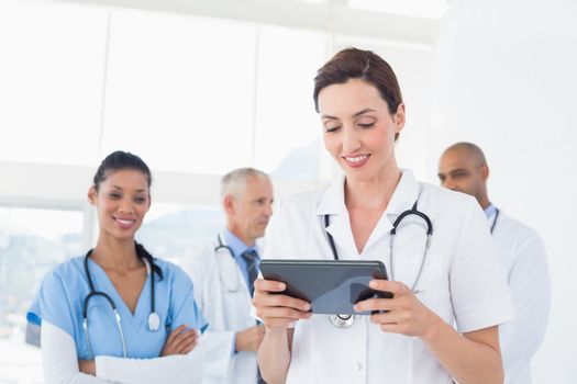 Confident female doctor holding tablet with her team behind