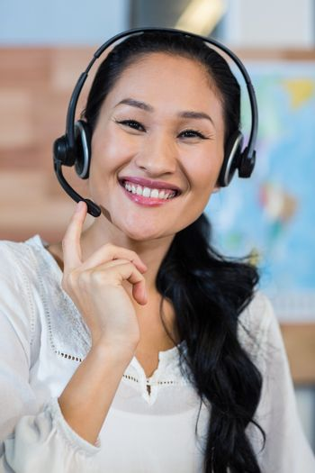Pretty travel agent smiling at camera in the office