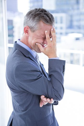 Troubled businessman holding his head