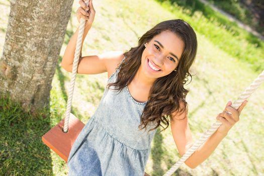Pretty brunette swinging in park