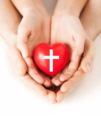 religion, christianity and charity concept - family couple hands holding red heart with christian cross symbol