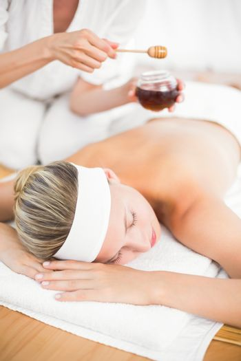Therapist waxing womans back at spa center