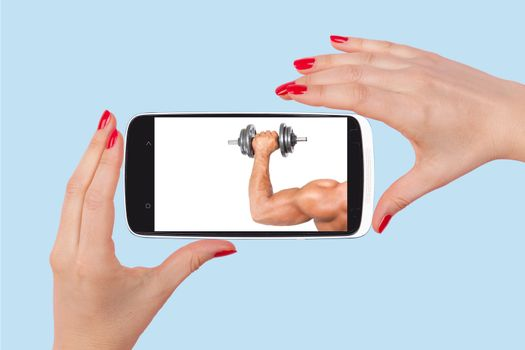 Online dating. Female hands holding smartphone with picture of handsome man isolated on pink background. Flirting and relationship in the information age.