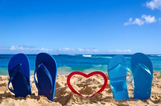Flip flops with heart shape on the sandy beach in Hawaii, Kauai (romantic concept)