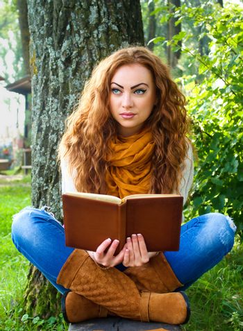 Beaytiful ginger-haired woman reading a book in park sitting on the bench