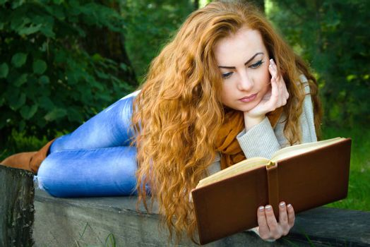 Beautiful ginger-haired woman reading a book in park lying on the bench