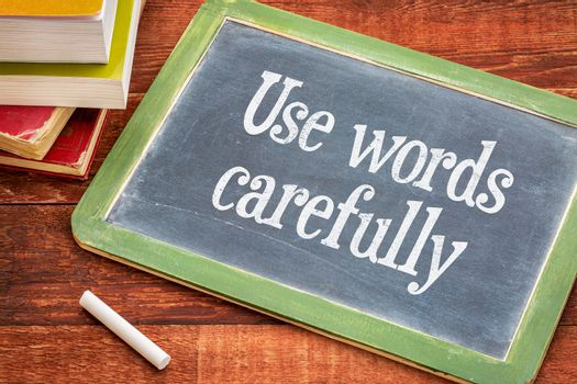 Use words carefully - text on a  slate blackboard with a white chalk and a stack of books against rustic wooden table