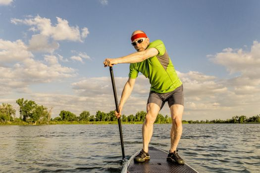 senior muscular male paddler enjoying paddling stand up paddleboard  on a local lake in Fort Collins, Colorado