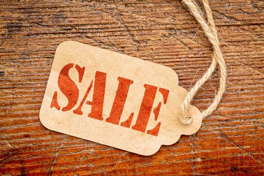 sale sign a paper price tag against rustic red painted barn wood - shopping concept