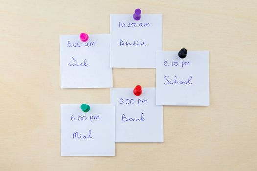 Memo notes as little white papers with appointments on pin-up board