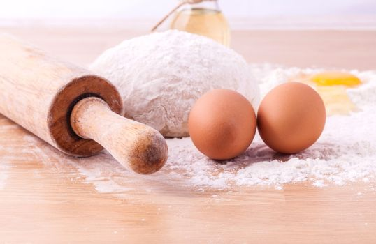 Baking ingredients including fresh eggs, flour and a rolling pin