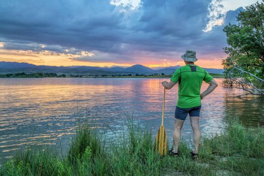 canoe paddler watching sunset over Rocky Mountains from a lake shore in Colorado near Loveland