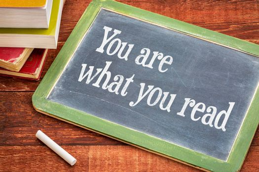 You are what you read - motivational phrase on a slate blackboard with a white chalk and a stack of books against rustic wooden table